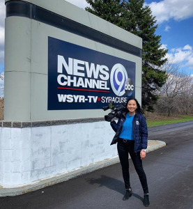 Adrienne in the field holding a camera outside in front of a News Channel 9 sign
