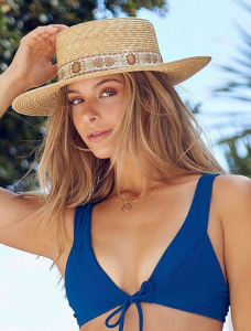 Ashley posing in a blue swimsuit and sun hat
