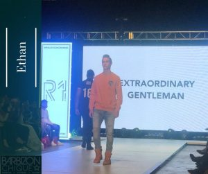 Ethan walking the runway with jeans, boots, and an orange long-sleeved shirt on
