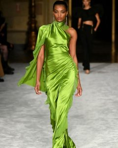 Leah walking the runway at NYFW wearing a green Christian Siriano gown