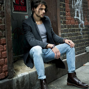 Sean modeling street wear sitting down against an alley wall