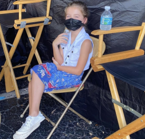 behind the scenes photo of Zoey seated on the movie set