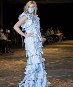 Paris Taylor posing on the runway wearing a surgical mask on her face and a dress made of surgical masks