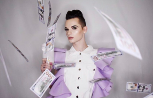 Braxton posing wearing makeup in an avant garde outfit with money flying around him