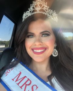 Laura in her car wearing her crown and sash and smiling for the camera
