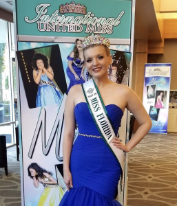 Skyler in front of a promotional sign in her crown and sash for International United Miss Florida