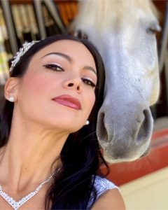 Yusby posing cheek to cheek with the head of a white horse