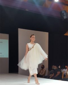 Abigail walking the runway in a white outfit