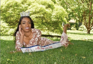 Sherrice laying in the grow with her title sash and crown