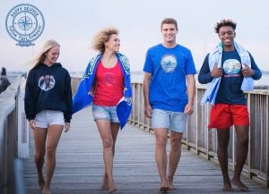 Red bank grads smiling and wearing casual clothing on a dock for The Happy Skipper clothing brand