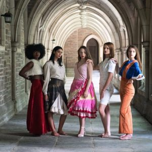 5 young women wearing styled long skirts an brightly colored outfits looking at different angles away fro the camera in an archway on the Princeton campus