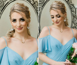 Naomi modeling in front of a decorative mirror in a blue bridal dress