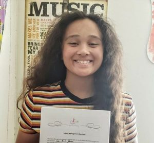 Cruz Johnson holding her signed contract