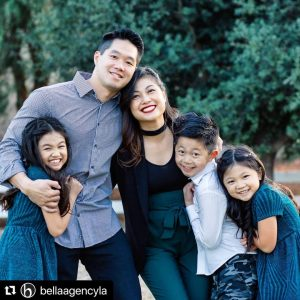 AJ Wong and his family, Mom, Dad, and two sisters, smiling in a group and hugging
