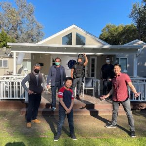 behind the scense shot of AJ Wong with his Dad on set in front of a house with camera crew