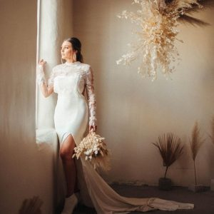 Rachel modeling a bridal dress and looking out of a window for the bridal shoot