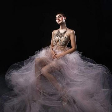 Sage modeling in a mystical, flowing dress on black backdrop
