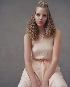 modeling shot of Skyler for the Aveda campaign wearing a curled hairstyle with a half updo