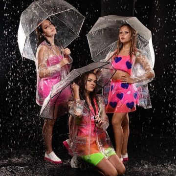Adelaide and Brenna modeling with umbrellas and rain gear for Electric Bubblegum