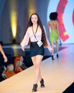 Andrea walking on the runway at Passport to Discovery modeling competition