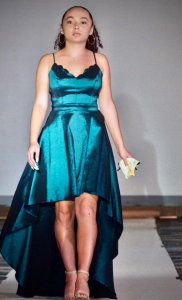 Briana Courtney walking on the runway wearing a shiny, teal gown