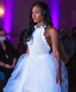 Jachelle modeling on the runway a white Lisa Jack Fashions dress at Coastal Fashion Week