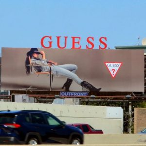 Jessica posing on the Guess billboard as seen from a road view