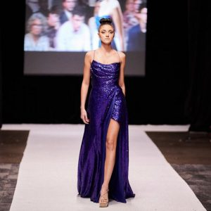 photo of Madison walking the runway in a long purple dress with an elaborate slit