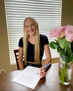Mikalah seated at a table smiling with her modeling contract