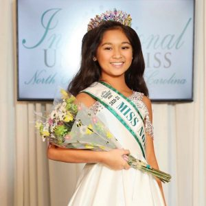 Raiah wearing her sash and crown at the International United Miss pageant