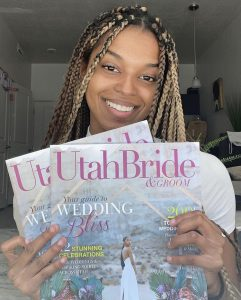 Sydney Williams smiling and holding up the Magazine she's featured in