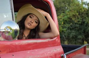 head shot of Ximena wearing a cowboy hat and leaning out of a red truck