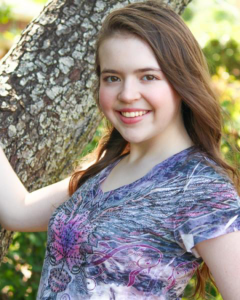 Lauren posing in a headshot in front of a tree