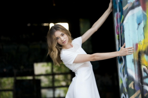 Bekah posing in a lean away from a graffitied wall