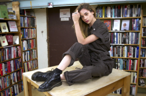 Modeling in a seated pose on top of a table surrounded by bookshelves