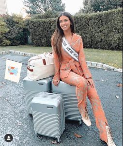 body shot of Gina wearing her Miss New Jersey sash and seated on luggage outside