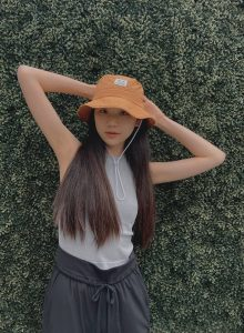 Lily in front of a green planted background modeling with an orange bucket hat on