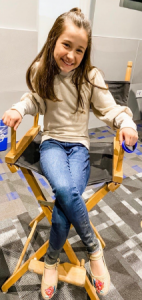 Jeanne sitting in an actor's chair smiling on set