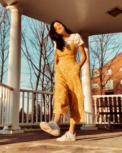 Josie in an action pose on her front porch wearing a yellow romper