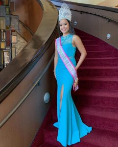 Photo of Kaley in a blue gown, sash, and crown on a winding staircase