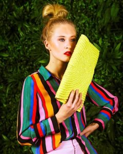 Krysten in a bright colored shirt product modeling with a yellow clutch bag
