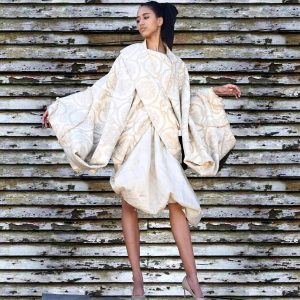 Mayeline modeling in a large tapestry garment for the editorial