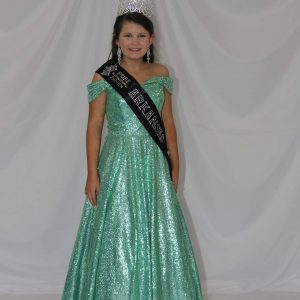 Ragan posing in a teal gown with her winning sash and crown