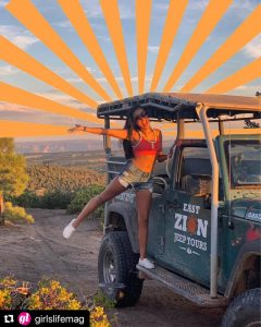 Repost Image from Girls' Life Instagram of Riley standing with her arm and leg out on the side of a Jeep and looking excited with edited yellow sun rays above her