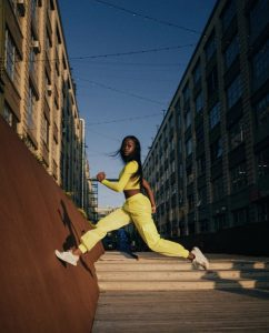Saskia running on the streets of New York, mid air capture of her jumping and wearing a yellow jumpsuit