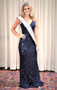 Taylor posing in dress, sash, and crown