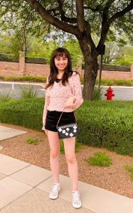 body shot of Tiffany outside wearing a fashionable outfit and purse