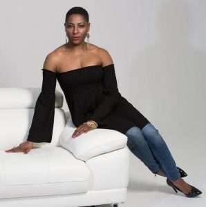 Yemi looking professional in a seated model's pose on a white couch