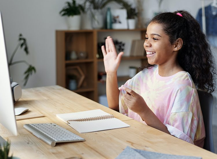 Young Girl sitting at a computer waving and smiling at the screen