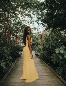 Saskia modeling outside in a long yellow dress and smiling
